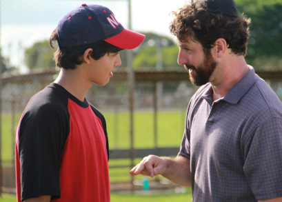Rabbi Brookstein (Sean McConaghy) and Josh (Luca Oriel) talking on the baseball field.