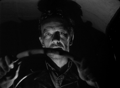 William Talman, as the titular character, takes the wheel in Ida Lupino's THE HITCH-HIKER.