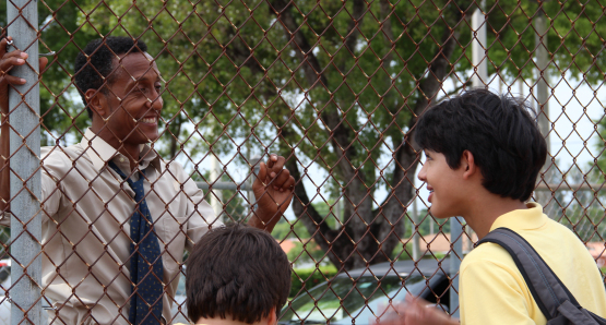 Byrd (Andre Royo) talking to Josh (Luca Oriel) and Tony (Alex Higgins) by the basketball court.